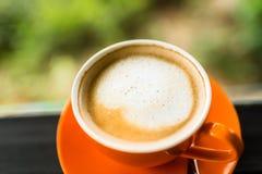 Taza de café anaranjada con el bokeh de la naturaleza Imagenes de archivo
