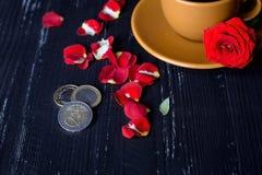 Taza de café anaranjada con los pétalos color de rosa y las monedas euro en el fondo negro imagen de archivo