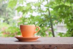 Taza de café anaranjada en el tablero de la mesa foto de archivo