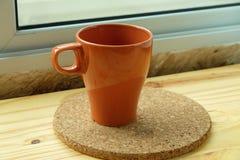 Taza de café anaranjada en la tabla de madera Fotografía de archivo libre de regalías