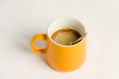 Taza de café anaranjada en un fondo blanco foto de archivo