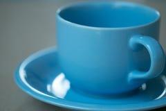 Taza de café azul en un fondo gris Foto de archivo