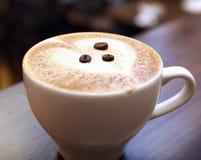 Taza de café blanca con las habas Imagenes de archivo