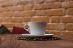 Taza de café blanca con los granos Imagen de archivo