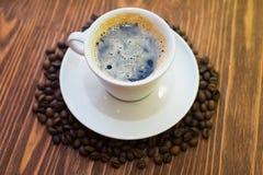 Taza de café blanca con los granos Fotos de archivo libres de regalías