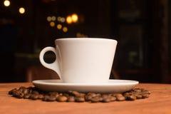 Taza de café blanca con los granos Fotos de archivo