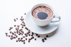 Taza de café blanca con los granos de café en la tabla blanca Imagen de archivo
