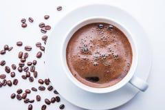 Taza de café blanca con los granos de café en la tabla blanca Visión superior Imagen de archivo libre de regalías