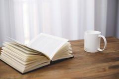 Taza de café blanca con un libro Fotos de archivo libres de regalías