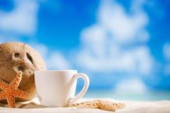 Taza de café blanca del café express con el océano, la concha marina, la playa y el seasc Imagen de archivo