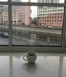 Taza de café blanca en la ventana foto de archivo libre de regalías