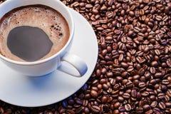 Taza de café blanca en los granos de café imagen de archivo