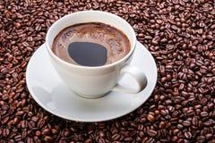 Taza de café blanca en los granos de café Foto de archivo libre de regalías