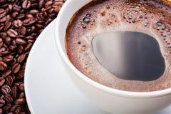 Taza de café blanca en los granos de café Fotos de archivo