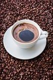 Taza de café blanca en los granos de café Imagen de archivo libre de regalías