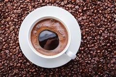 Taza de café blanca en los granos de café Visión superior Foto de archivo
