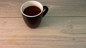 Taza de café blanco y negro con la mancha del café a bordo imagenes de archivo