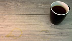 Taza de café blanco y negro con la mancha del café en piso Imagen de archivo libre de regalías
