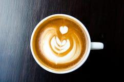 Taza de café borrosa con arte hermoso del Latte en backgrou negro Fotos de archivo