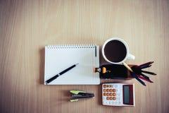 Taza de café, calculadora, grapadora, cuaderno, pluma colorida Imágenes de archivo libres de regalías