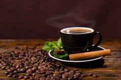 Taza de café caliente con el palillo y las habas de canela Imagenes de archivo