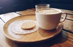 Taza de café caliente con las galletas, luz del sol en fondo Fotos de archivo
