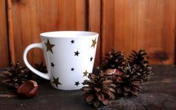 Taza de café caliente con leche en el fondo, el cono y las castañas de madera como decoración Estilo retro Domingo se relajan y a Imagen de archivo libre de regalías