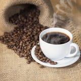 Taza de café caliente con los granos de café Imágenes de archivo libres de regalías