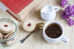 Taza de café caliente con los libros, la leche y las flores en la tabla de madera Foto de archivo