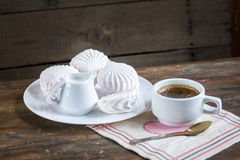 Taza de café caliente con los libros, la leche y las flores en la tabla de madera Fotografía de archivo libre de regalías
