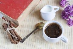 Taza de café caliente con los libros, la leche y las flores en la tabla de madera Imágenes de archivo libres de regalías