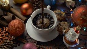 Taza de café caliente con los palillos de canela en la tabla de madera entre decoraciones de la Navidad almacen de video