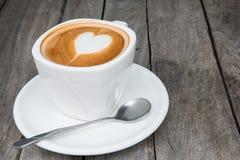 Taza de café caliente del arte del latte en la tabla de madera Fotografía de archivo