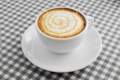 Taza de café caliente del capuchino con arte del Latte en la tabla de la tela escocesa Imagen de archivo