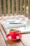 Taza de café caliente en la estación de trabajo de madera Fotos de archivo