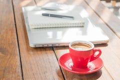 Taza de café caliente en la estación de trabajo de madera Fotos de archivo libres de regalías