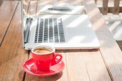 Taza de café caliente en la estación de trabajo de madera Imágenes de archivo libres de regalías