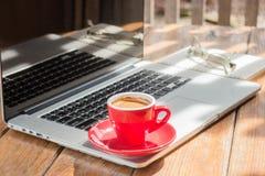Taza de café caliente en la estación de trabajo de madera Foto de archivo libre de regalías