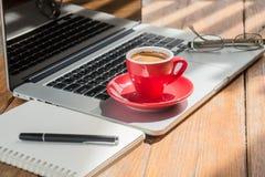Taza de café caliente en la estación de trabajo de madera Imagen de archivo libre de regalías