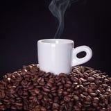 Taza de café caliente encima de los granos de café con el fondo negro Imágenes de archivo libres de regalías