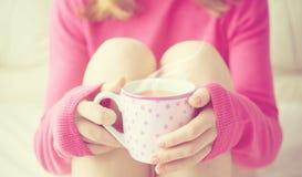 Taza de café caliente que se calienta en las manos de una muchacha imagenes de archivo