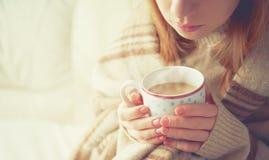 Taza de café caliente que se calienta en las manos de una muchacha Foto de archivo