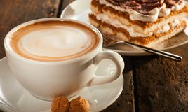 Taza de café de cerámica blanca con el postre imagenes de archivo