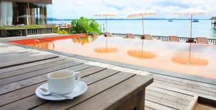 Taza de café cerca de la playa y de la piscina Imagen de archivo libre de regalías