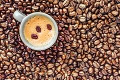 Taza de café colocada en una cama de los granos de café Imagen de archivo