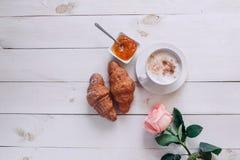 Taza de café con buena mañana del cruasán, de la rosa, del atasco y de las notas en la tabla rústica blanca desde arriba, acogedo Fotografía de archivo libre de regalías