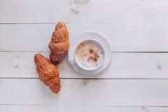 Taza de café con buena mañana del cruasán y de las notas en la tabla rústica blanca desde arriba, acogedor y sabroso desayuno, vi Imágenes de archivo libres de regalías