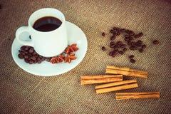 Taza de café con canela, anís y habas foto de archivo