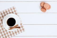 Taza de café con canela y macarrones en un fondo blanco Foto de archivo