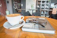 Taza de café con cristalería en el libro en la tabla Fotos de archivo libres de regalías